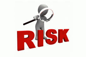 stickman with magnifying glass looking at the word RISK