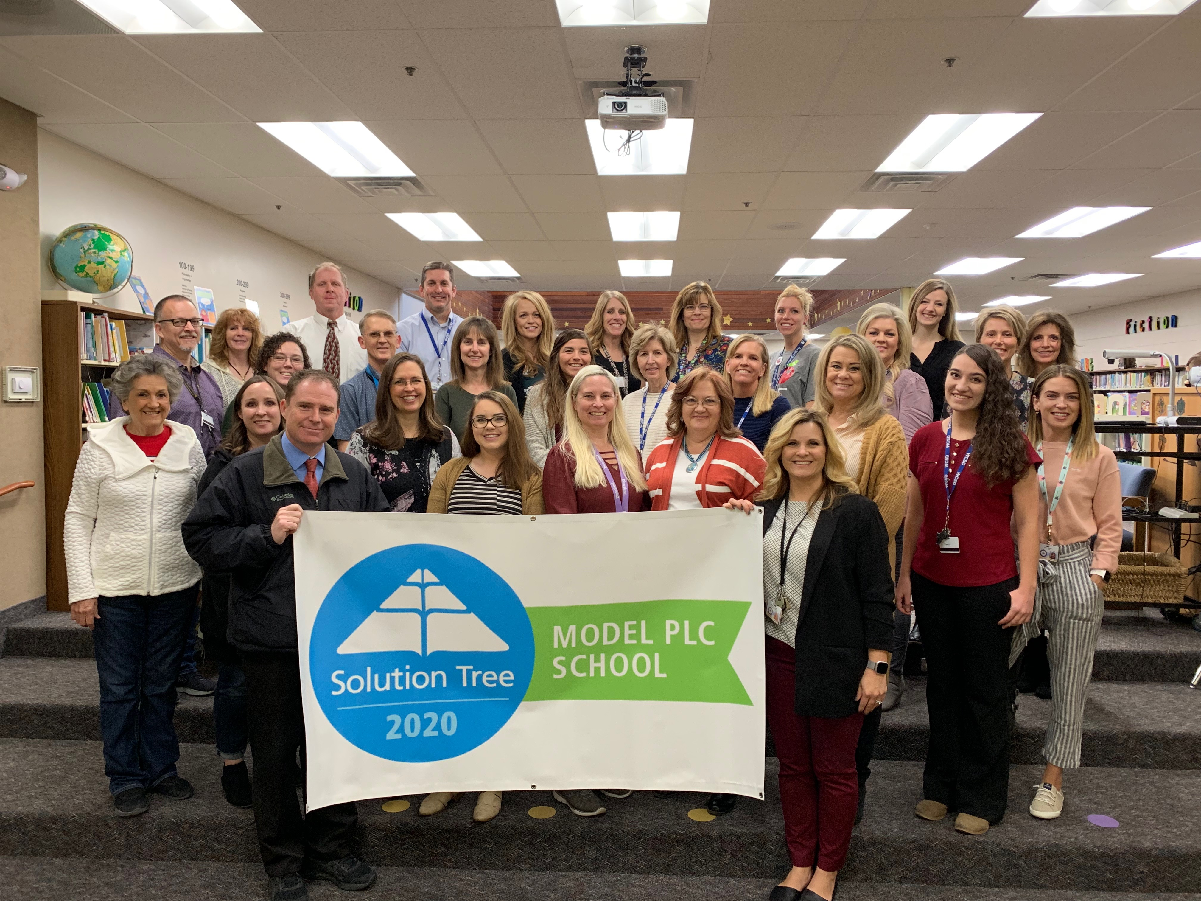 "Panorama School Staff with banner that says ""Solution Tree 202 - Model PLC School"""